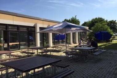 2015 Juli Erweiterung des Mensa-Komforts - Sitz-Tisch-Gruppen und Sonnenschirme ermöglichen Essen im Freien.